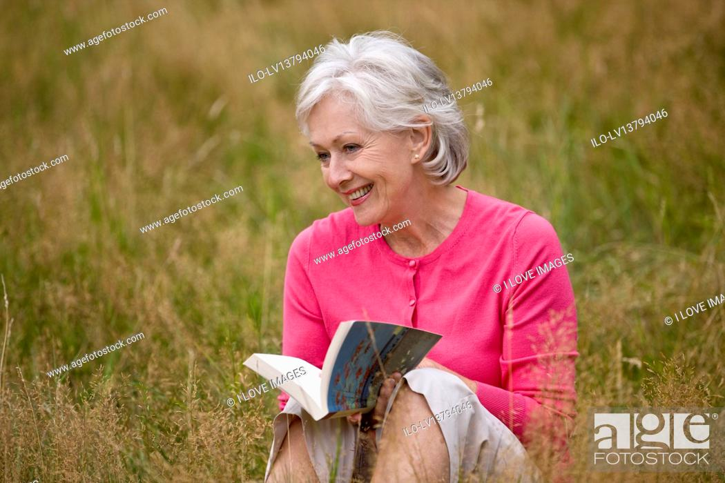 Stock Photo: A senior woman sitting on the grass, reading a book.