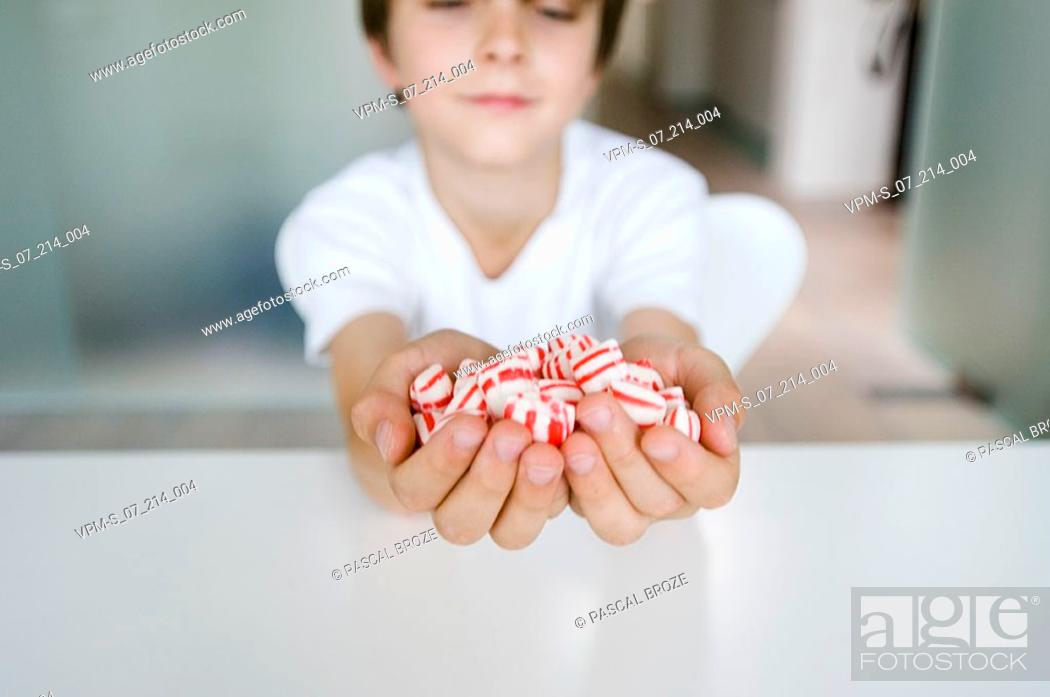 Stock Photo: Close-up of a boy holding a handful of candies.