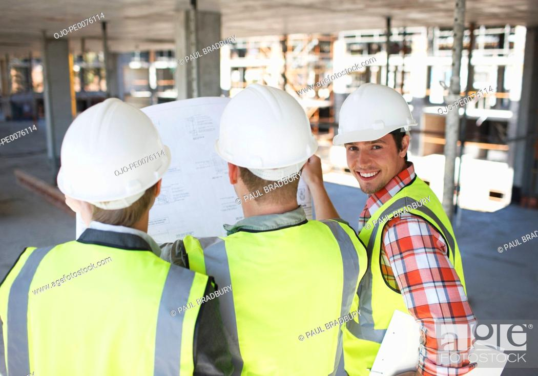 Stock Photo: Construction workers looking at blueprint on construction site.