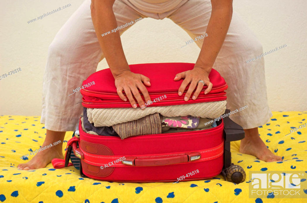Stock Photo: Woman trying to squeeze her packed travel case shut.