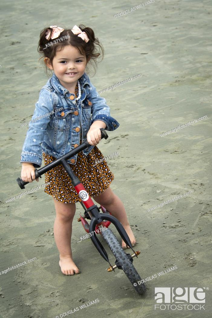 Imagen: A three year old girl on her push bike on the beach at Tofino, BC, Canada.