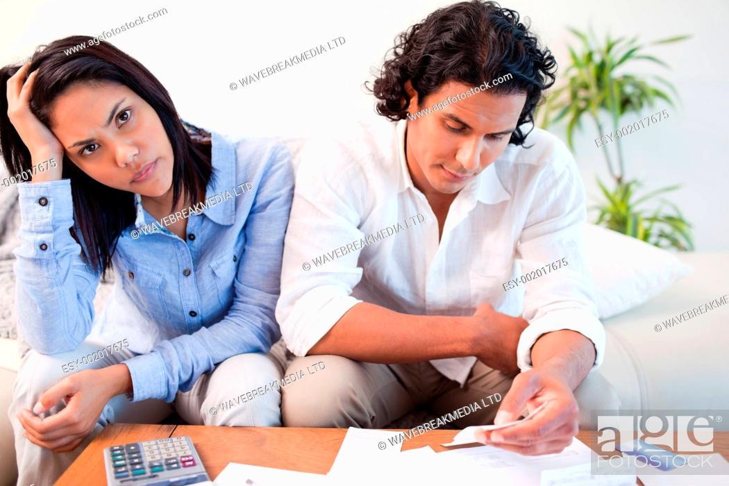 Stock Photo: Sad young couple checking their bills.