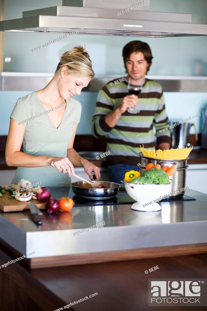 Stock Photo: Young couple in modern kitchen, cooking, drinking red wine.
