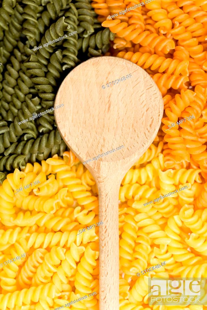 Stock Photo: Wooden spoon, green and yellow noodles.