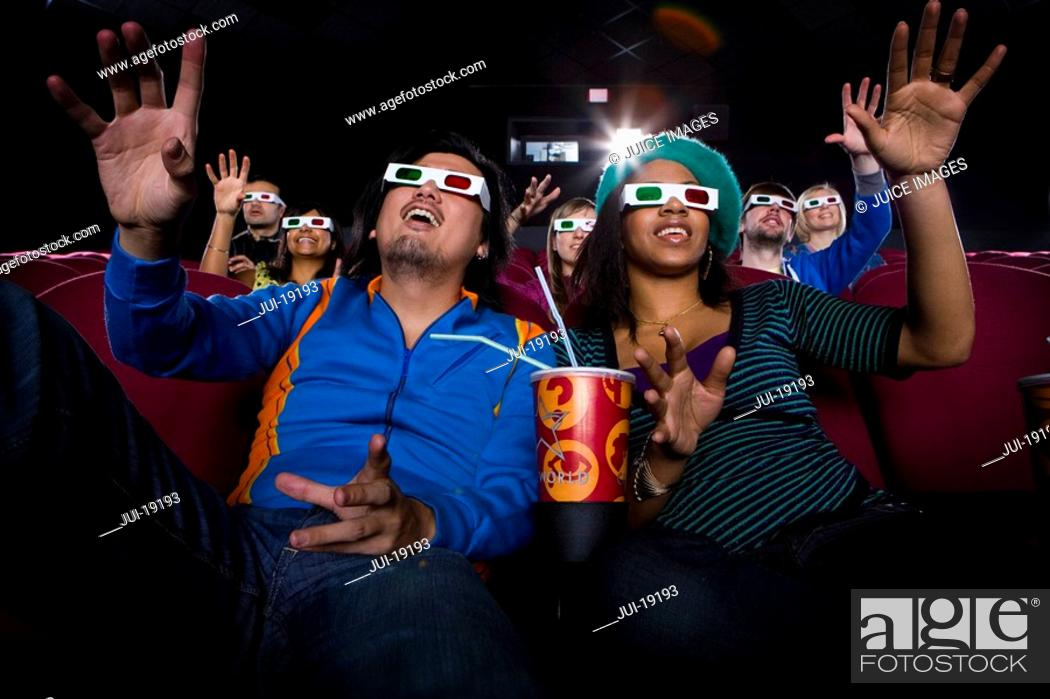 Stock Photo: Couple in cinema wearing 3D glasses, smiling, low angle view.