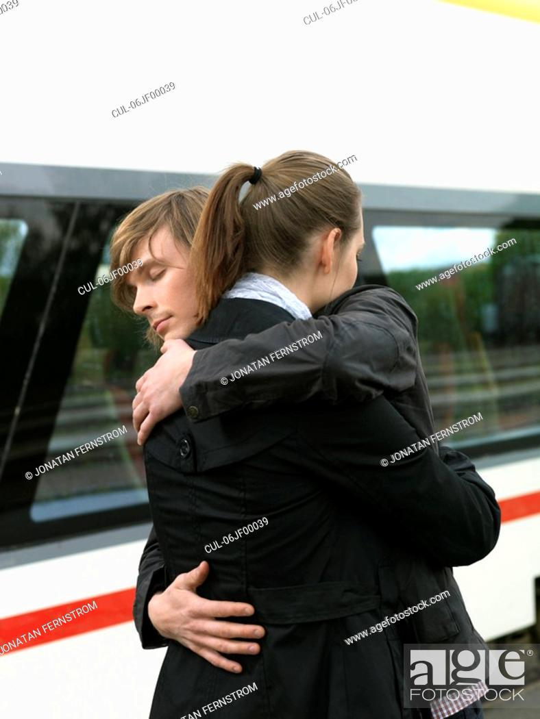 Stock Photo: Couple embracing on train station.