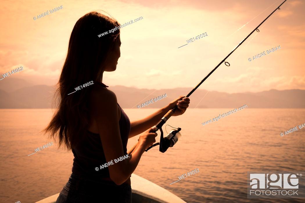 Stock Photo: Young woman holding fishing pole at sunset. Banderas Bay - Pacific Ocean, Puerto Vallarta, Mexico.