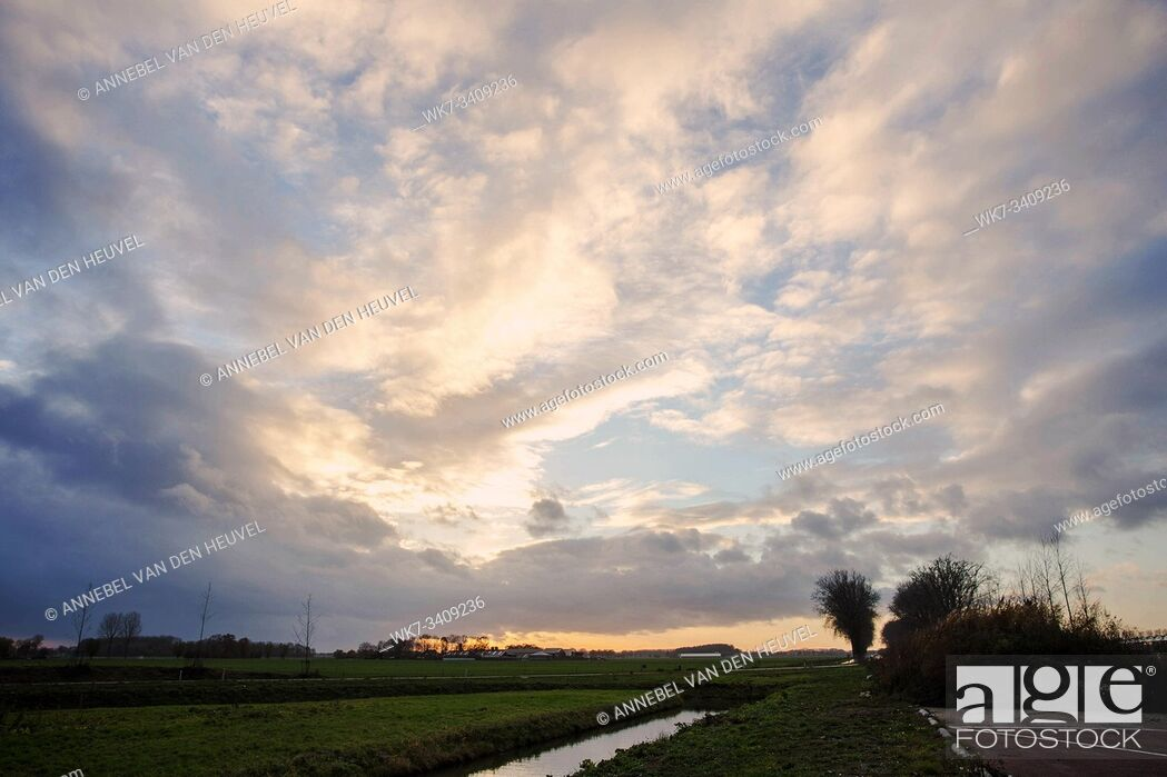 Photo de stock: Natural Sunset Sunrise Over Field Or Meadow. Bright Dramatic Sky And Dark Ground. Countryside Landscape Under Scenic Colorful Sky At Sunset Dawn Sunrise.