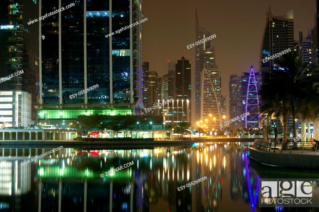 Stock Photo: Dubai, United Arab Emirates - April 25, 2018. High skyscrapers of the business city centers, located near the seaport. Night time urban landscape.