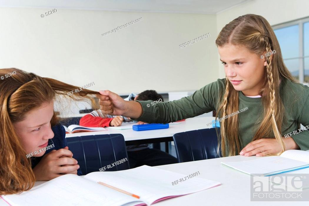 Stock Photo: School girls 10-13 in classroom, one girl pulling other girls hair, bullying.