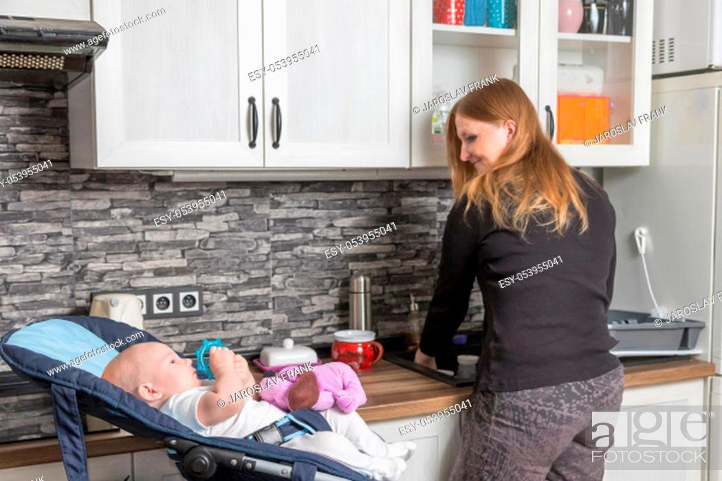 Stock Photo: Cute baby boy is lying comfortable in child seat while his mother is washing dishes in the kitchen.