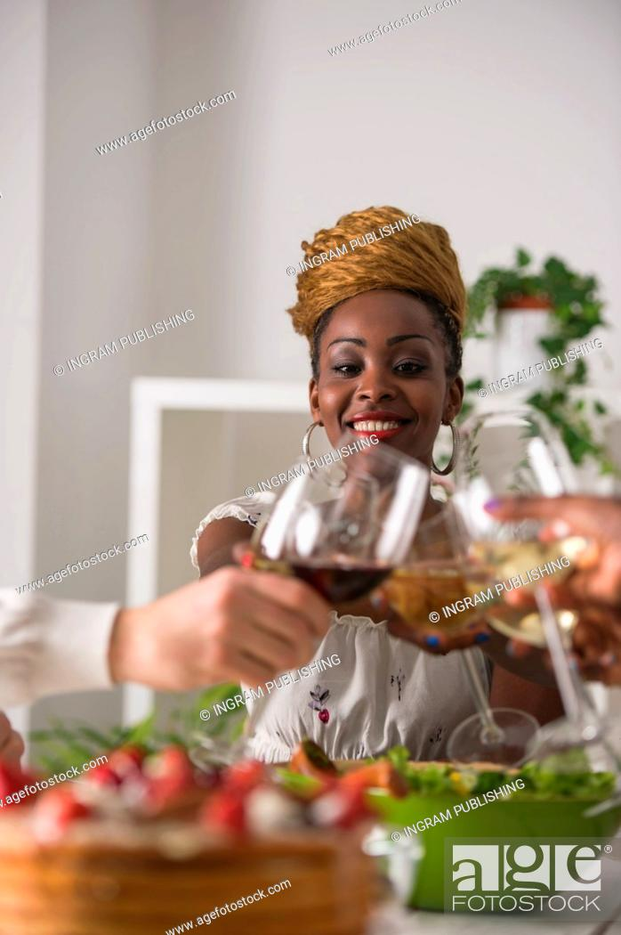 Stock Photo: Multiracial Group Of Young Friends Enjoying Meal at Home.