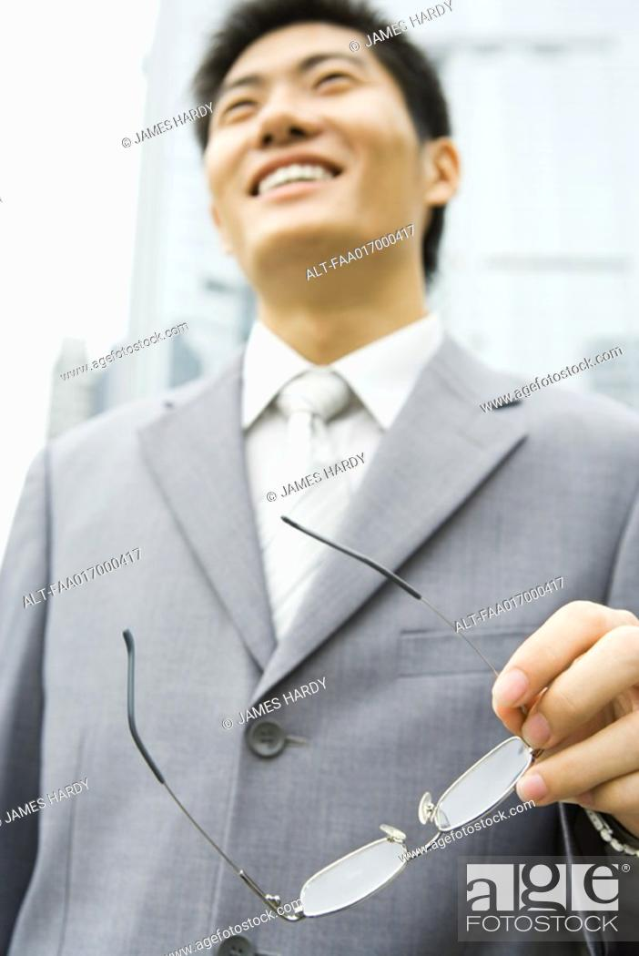 Stock Photo: Businessman holding glasses, low angle view.