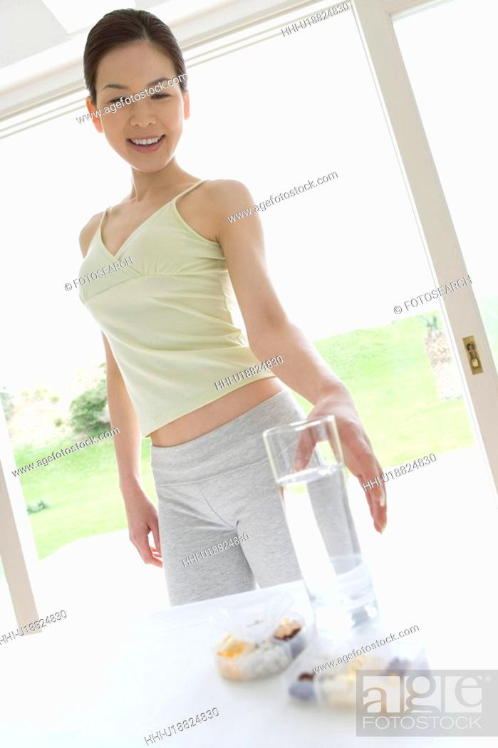 Stock Photo: Young woman taking supplements and water, low angle view.