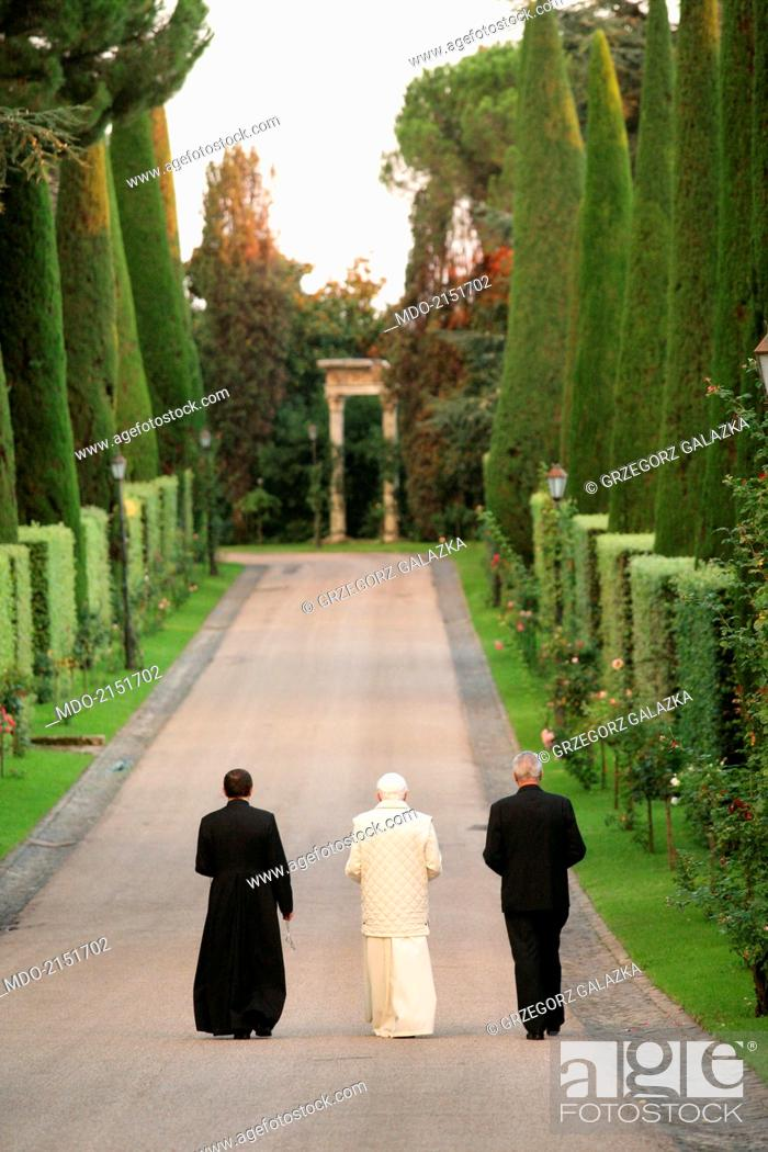 Stock Photo: The pope Benedict XVI (Joseph Aloisius Ratzinger) walking in the garden and saying the rosary with the archbishop Mieczyslaw Mokrzycki and the butler Angelo.