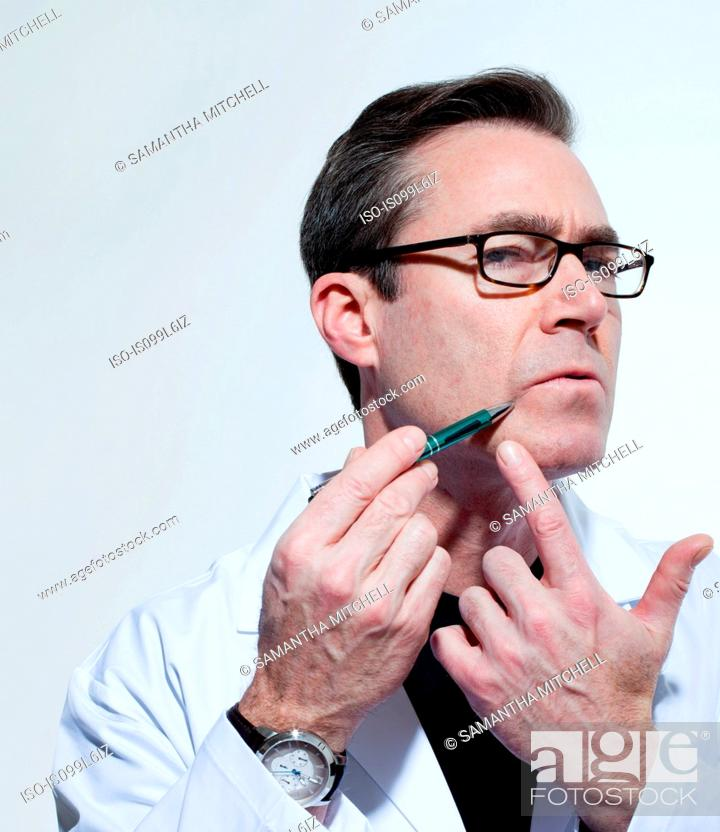 Stock Photo: Plastic surgeon using pen to point to his face.