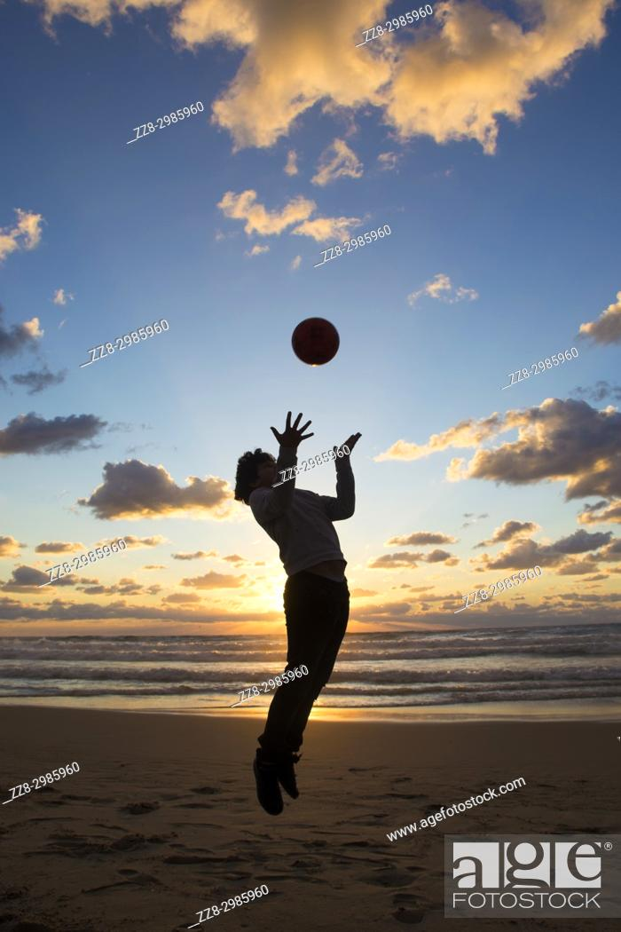 Stock Photo: Full length, silhouette of a little boy playing with the ball on the beach at sunset.