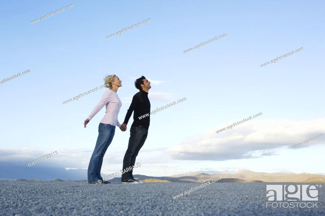 Stock Photo: Man and woman leaning into the wind.