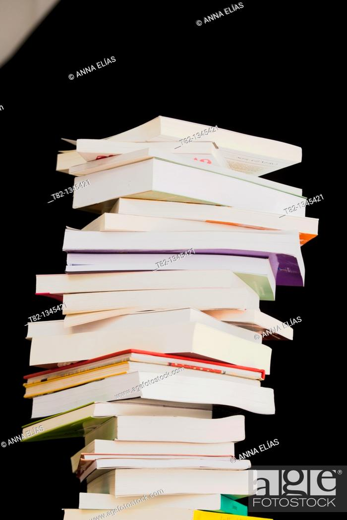 Stock Photo: books stacked on a black background.