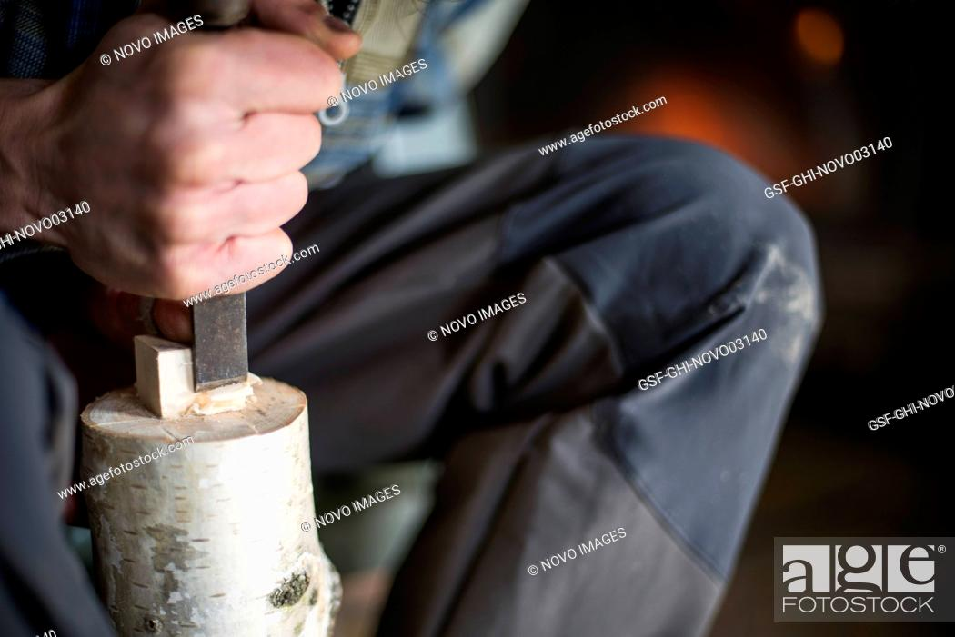 Stock Photo: Hand of Woodworker using Chisel on Piece of Wood.
