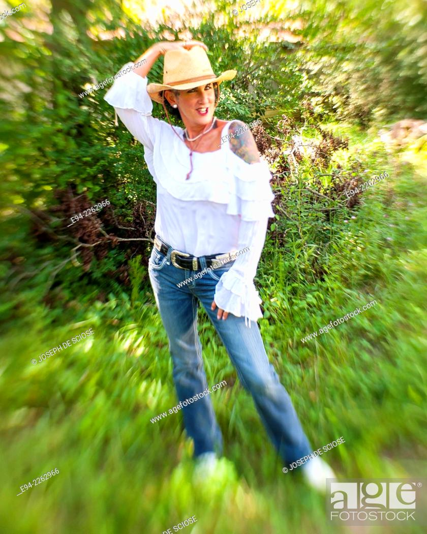 Stock Photo: 54 year old brunette woman with tattoos in outdoor setting wearing a straw hat and blue jeans looking at the camera.