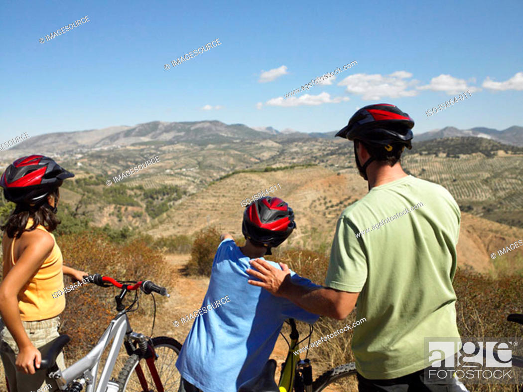 Stock Photo: Cyclist father and children looking at view.