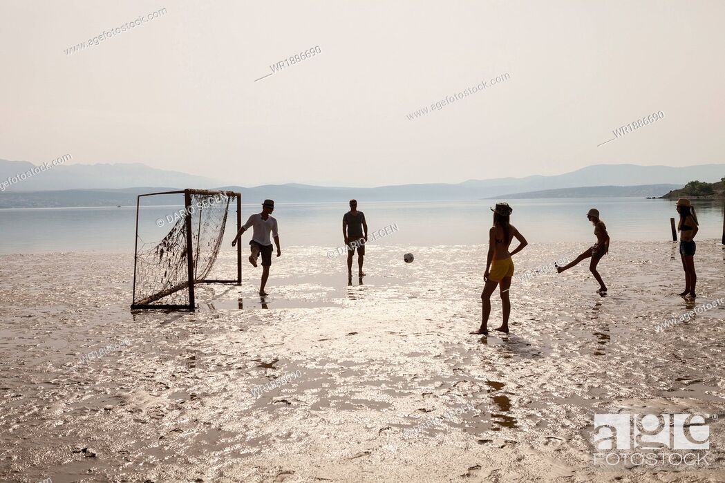 Stock Photo: Croatia, Young people on beach playing soccer.