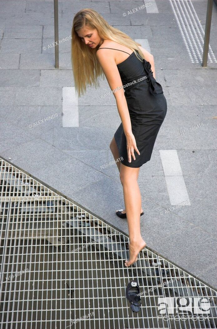 Stock Photo: Young woman looses her high heeled shoe in a pavement drain cover.