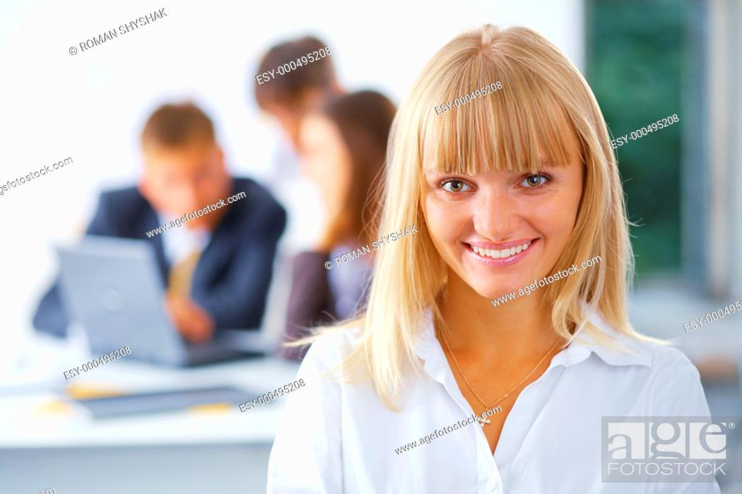Stock Photo: Young happy business woman with her working friend at the background.