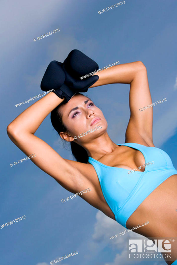 Stock Photo: Low angle view of a young woman wearing boxing gloves.