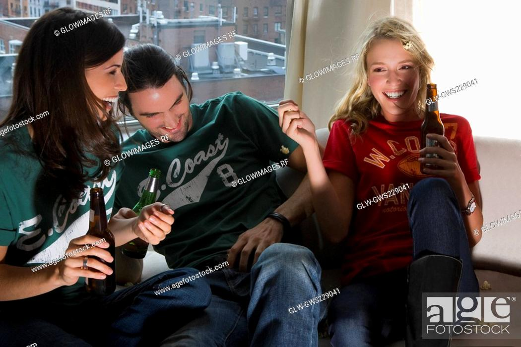 Stock Photo: Two young women and a young man holding beer bottles.