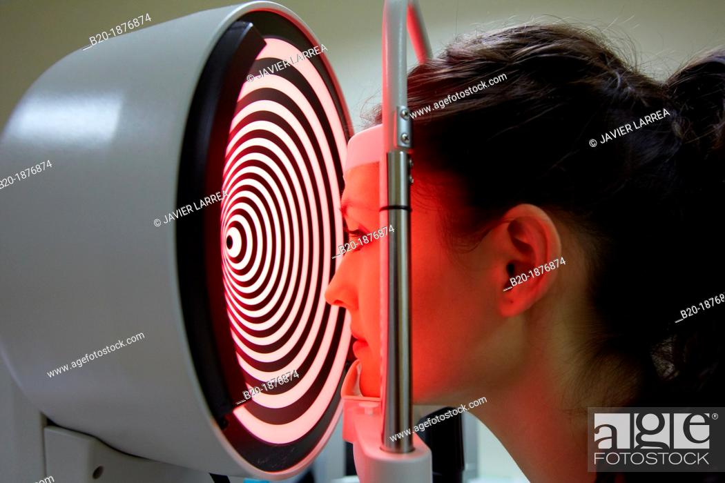 Stock Photo: Eye examination  Patient having a corneal topography measurement made of her eye  The device at centre projects bright rings onto the eye.