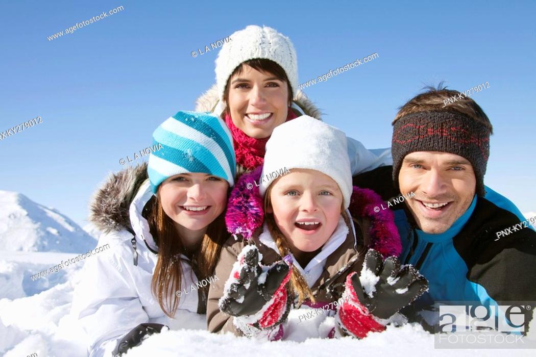 Stock Photo: Parents and children lying in snow, smiling at camera.