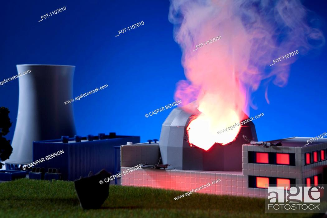 Stock Photo: A model built to scale of a nuclear power plant on fire.