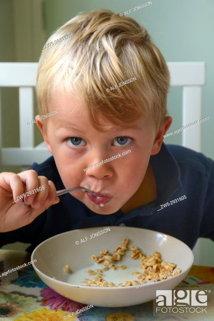 Stock Photo: Little boy, four years old, have lunch with cereals with milk.