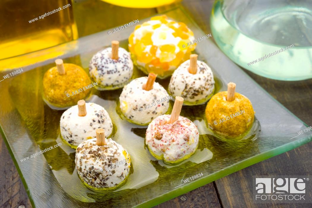 Photo de stock: cheese balls with spices in olive oil, on rustic wood.
