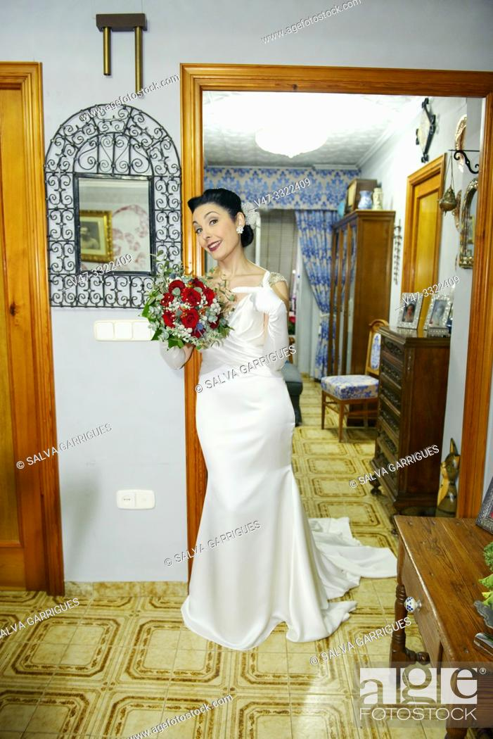 Imagen: Portrait to the bride with the wedding bouquet in her house, the day of the wedding, Carcaixent, Valencia, Spain.