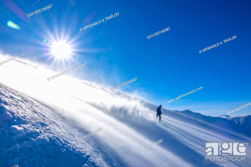 Imagen: Steep ski slope in windy sunny weather. A lonely unrecognizable snowboarder descends and picks up a lot of snow dust in the backlight of the sun.