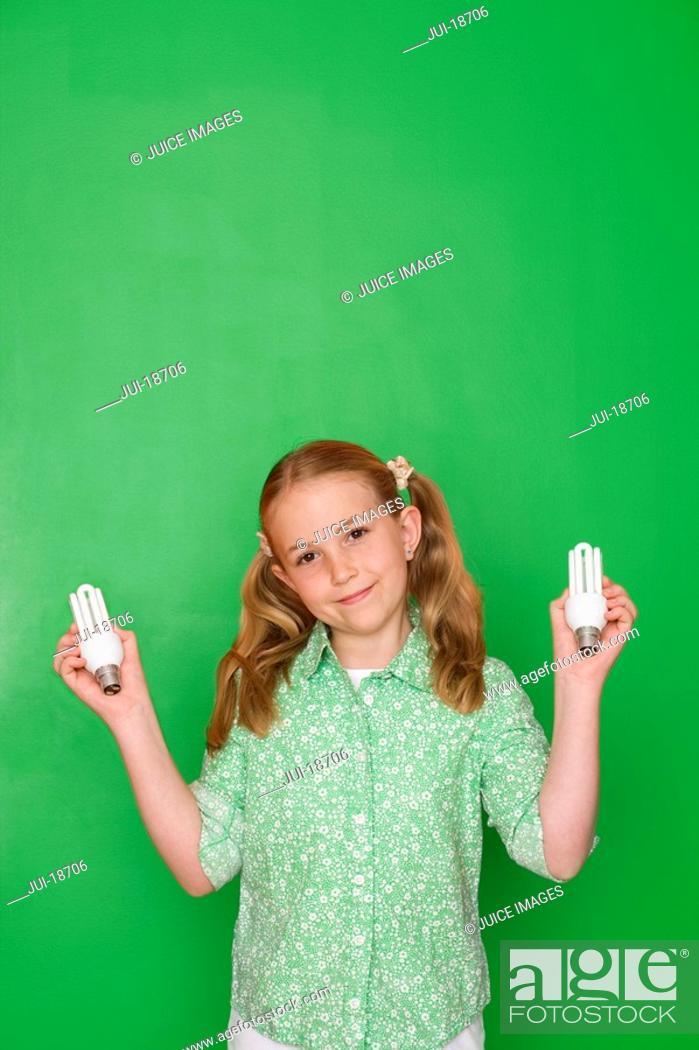 Stock Photo: Girl holding compact fluorescent light bulbs.
