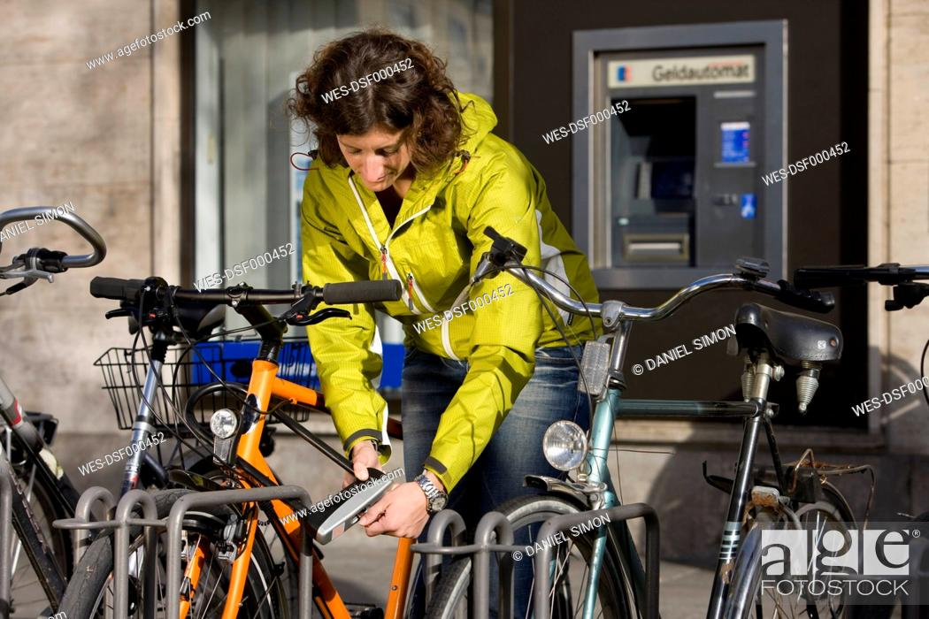 Stock Photo: Germany, Bavaria, Munich, Mid adult woman locking bicycle.