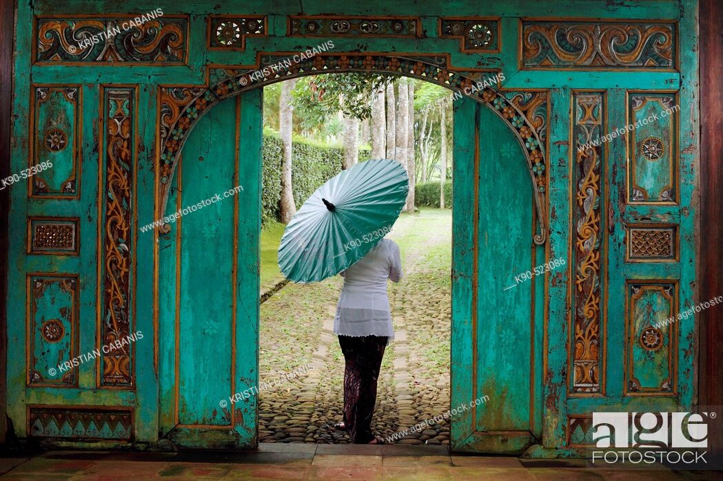 Stock Photo: Woman walking through a traditional, nicely carved door at Losari Coffee Plantation in West Java, Indonesia, South East Asia.