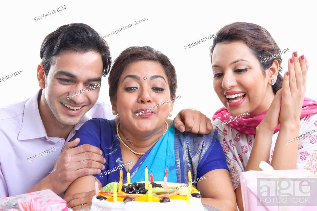Stock Photo: Woman blowing out candles on a birthday cake.