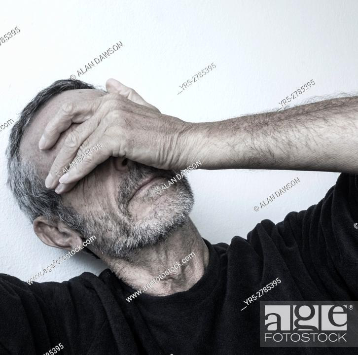 Stock Photo: Mature man with hand over eyes.