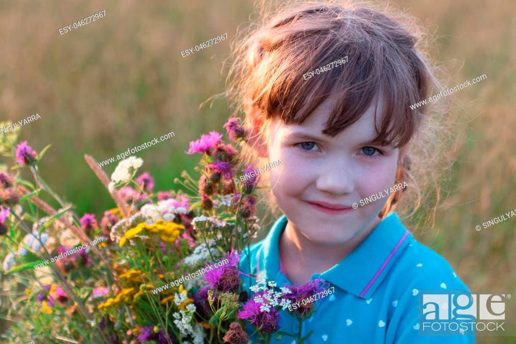Stock Photo: Little girl holds wild flowers and smiles in dry field at summer day.