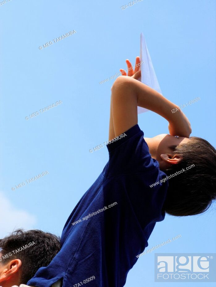 Imagen: Low angle view of a boy sitting on his father's shoulders flying a paper airplane.