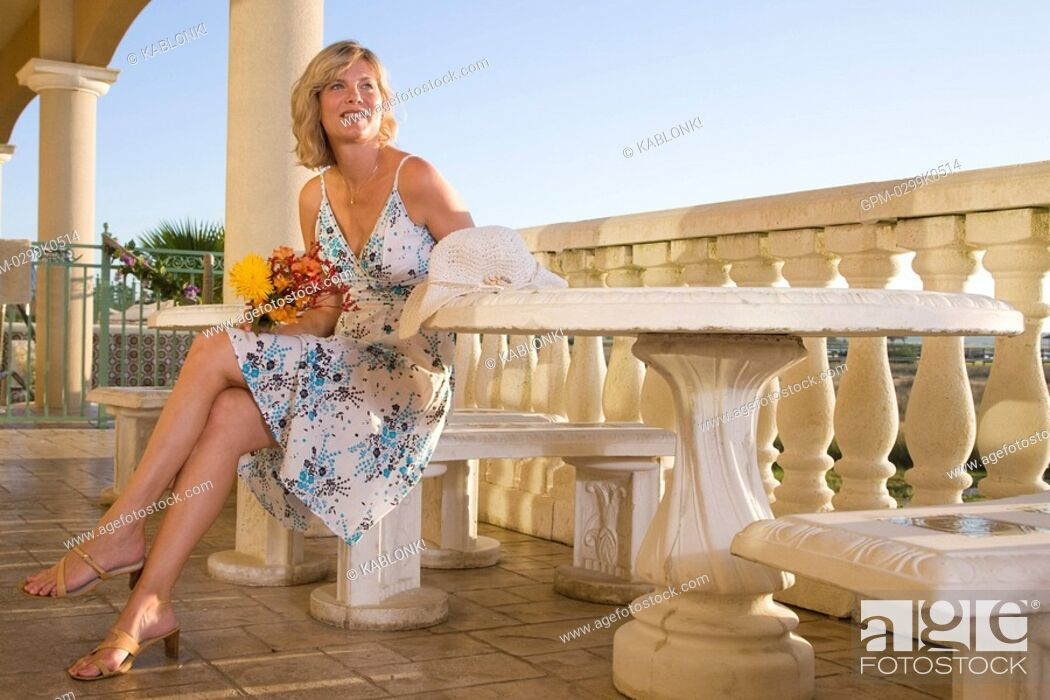 Imagen: Young woman sitting at table on balcony.