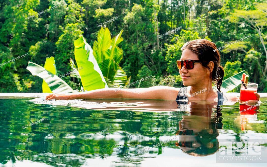 Photo de stock: Woman enjoying healthy drink in pool, Ubud, Bali, Indonesia.