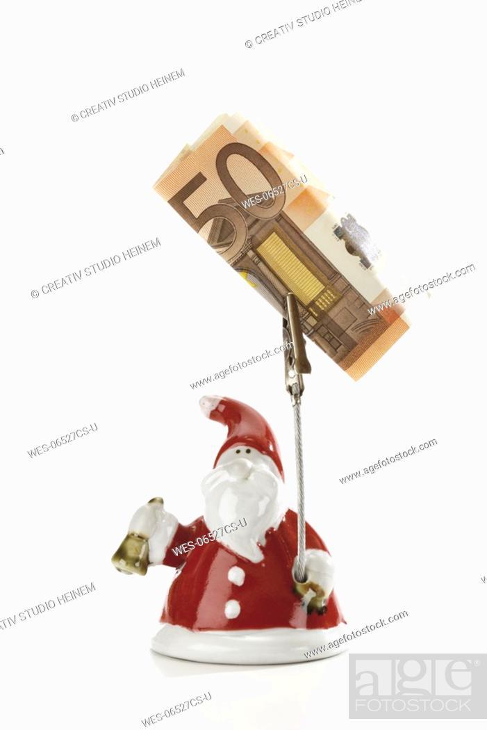 Stock Photo: Santa Claus Figurine holding Euro note.