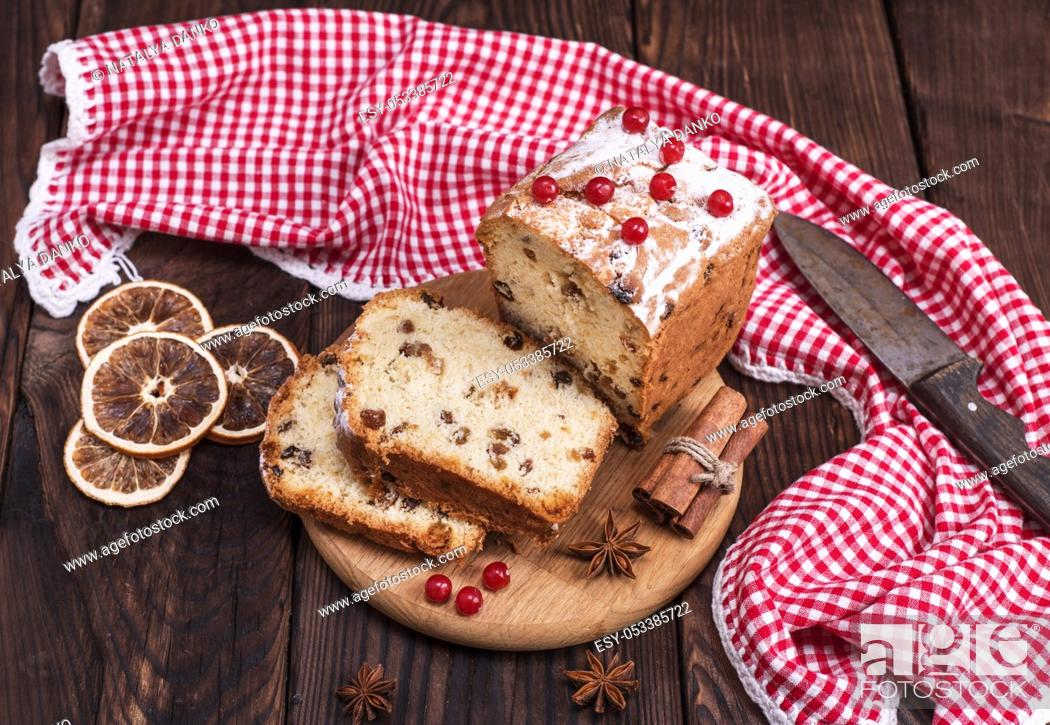 Stock Photo: rectangular fruit cake cut into slices on a wooden board, top view.