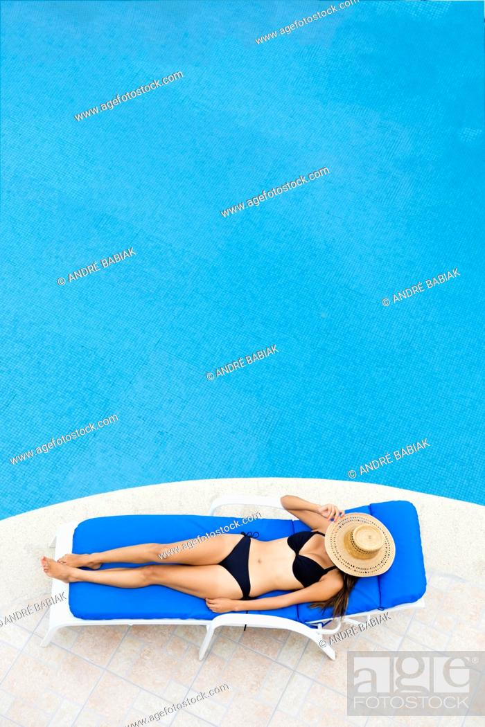 Stock Photo: Young woman relaxing on lounger at swimming pool. View from above with negative space.